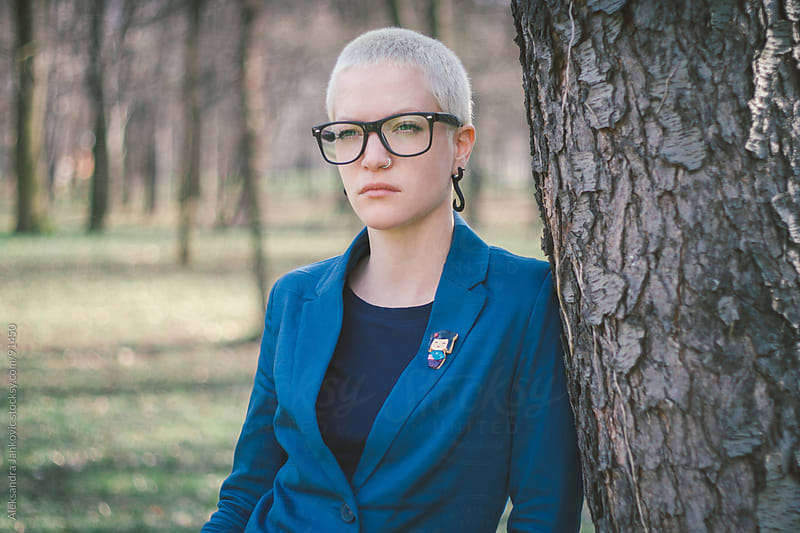 Portrait of a young, short-haired woman with glasses  by Aleksandra Jankovic for Stocksy United