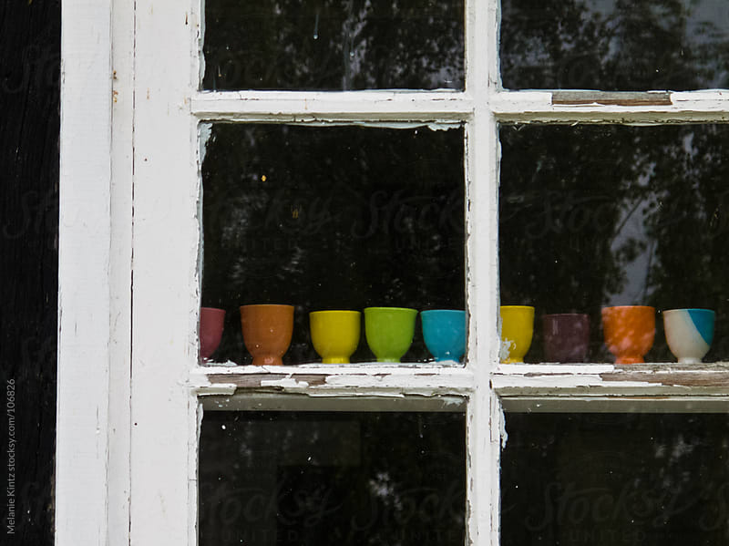 Colorful eggcups standing in a window by Melanie Kintz for Stocksy United