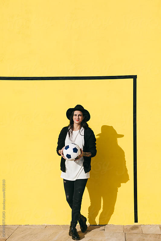 Portrait of an alternative woman holding a soccer ball in front of a yellow wall. by BONNINSTUDIO for Stocksy United