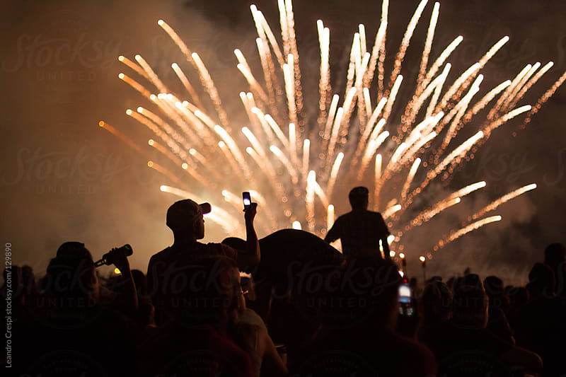 People enjoying fireworks show on new year by Leandro Crespi for Stocksy United