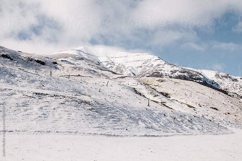 Snow covered mountain hillside on a brilliant sunny day by Justin Mullet for Stocksy United