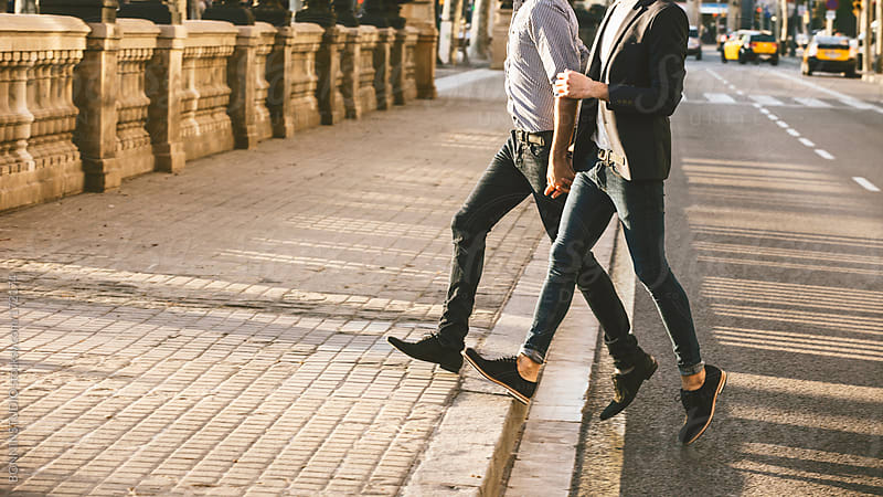 Portrait of gay couple holding hands and crossing road. by BONNINSTUDIO for Stocksy United