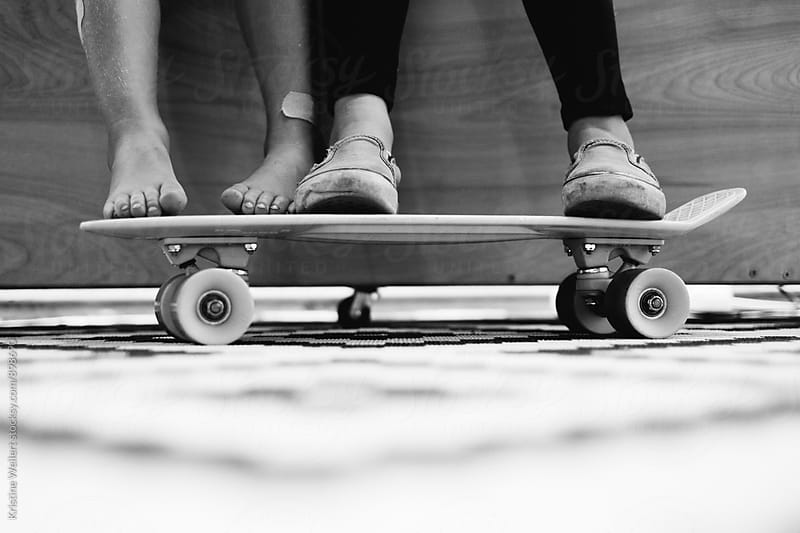Kids feet resting on skateboard by Kristine Weilert for Stocksy United