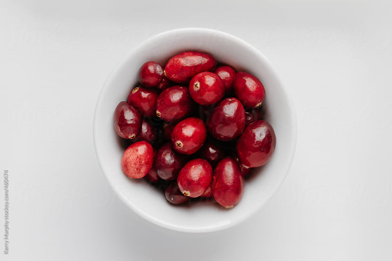 Cranberries in white bowl on white plate on red placemat by Kerry Murphy for Stocksy United