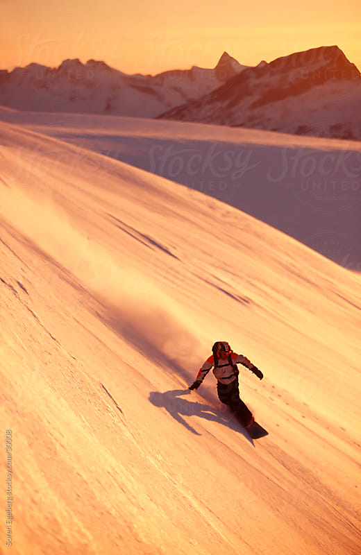 Young man snowboarding at sunset on orange snow in the mountains by Søren Egeberg Photography for Stocksy United