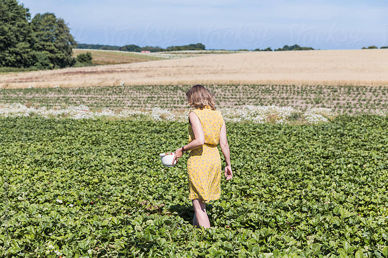 Woman in yellow dress walking in green field  by Lior + Lone for Stocksy United
