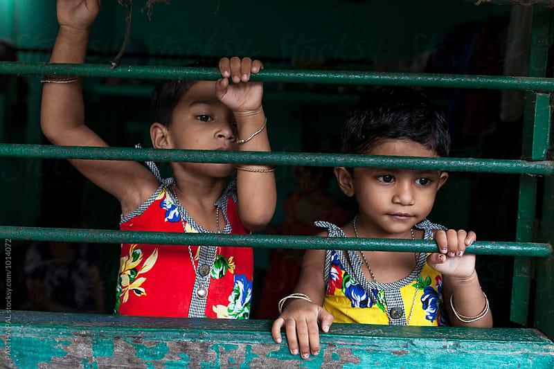 Twin girl behind a window by PARTHA PAL for Stocksy United