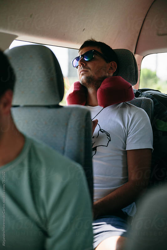 Young man sleeping comfortably in the back of a van during a road trip by Alejandro Moreno de Carlos for Stocksy United