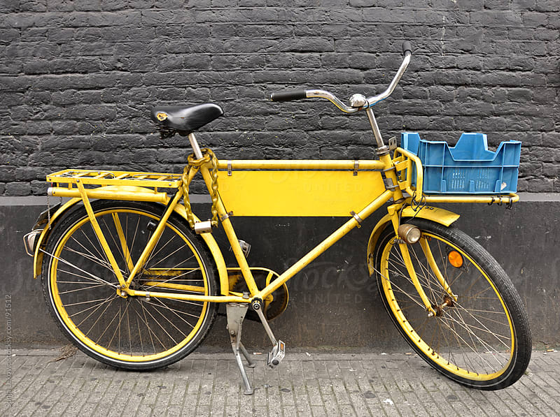 yellow bicycle against a gray wall by Sonja Lekovic for Stocksy United
