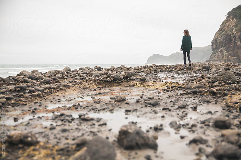 Woman standing on a rocky beach. by Robert Zaleski for Stocksy United