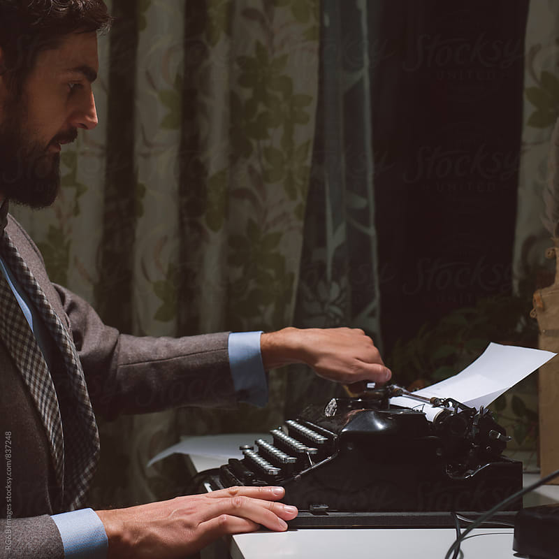 Man in vintage clothing inserting new paper into typewriter by RG&B Images for Stocksy United