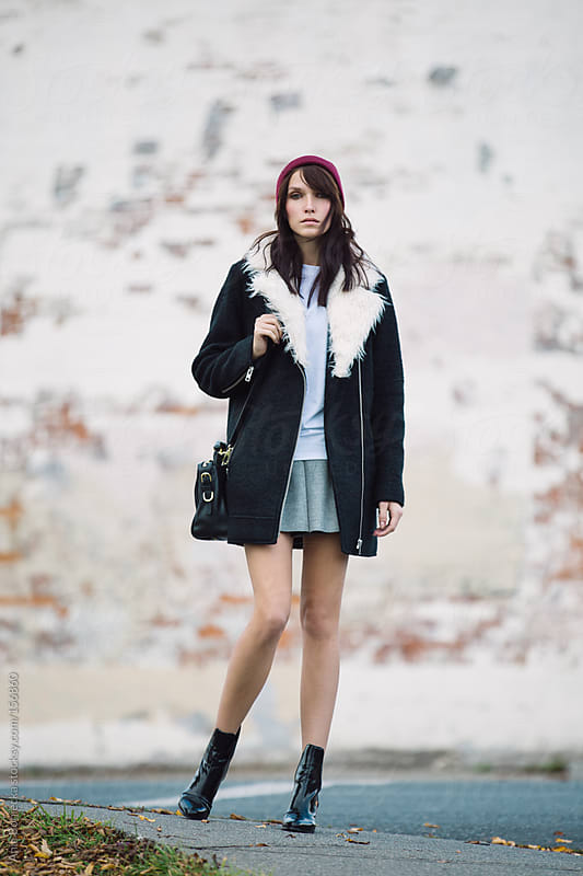 A street style photo of a beautiful woman with a red beanie by Ania Boniecka for Stocksy United