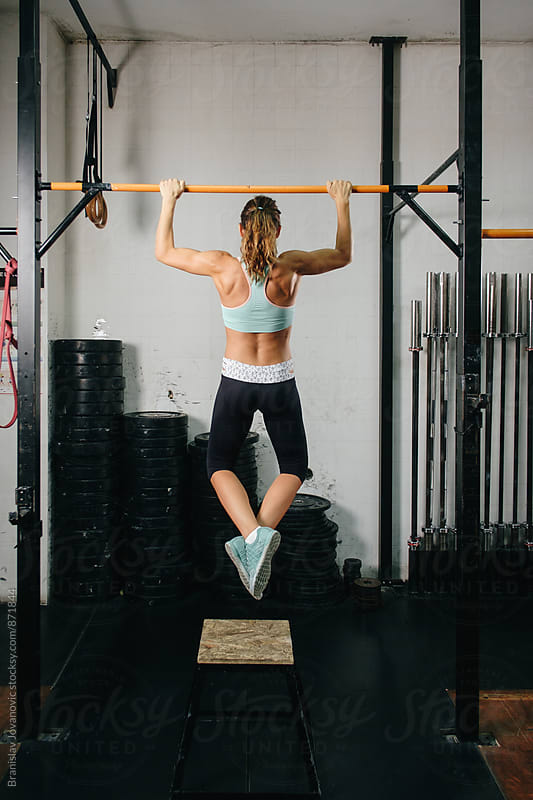 Woman Doing Chin-ups at the Gym by Brkati Krokodil for Stocksy United