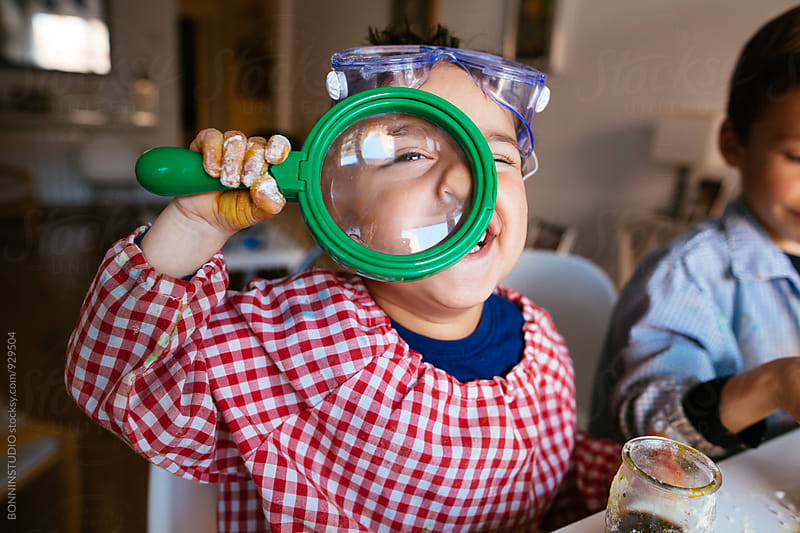 Little boy looking through magnifying glasses. by BONNINSTUDIO for Stocksy United