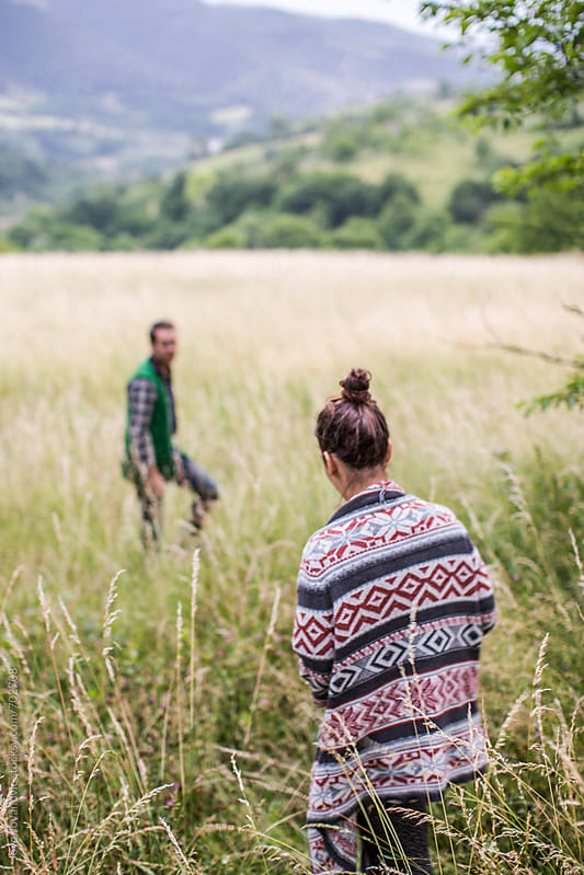Man and woman exploring the field of wild grass together by Jovo Jovanovic for Stocksy United