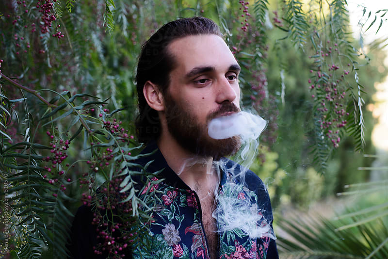 Male smoking in a natural garden in Andalusia by María Barba for Stocksy United