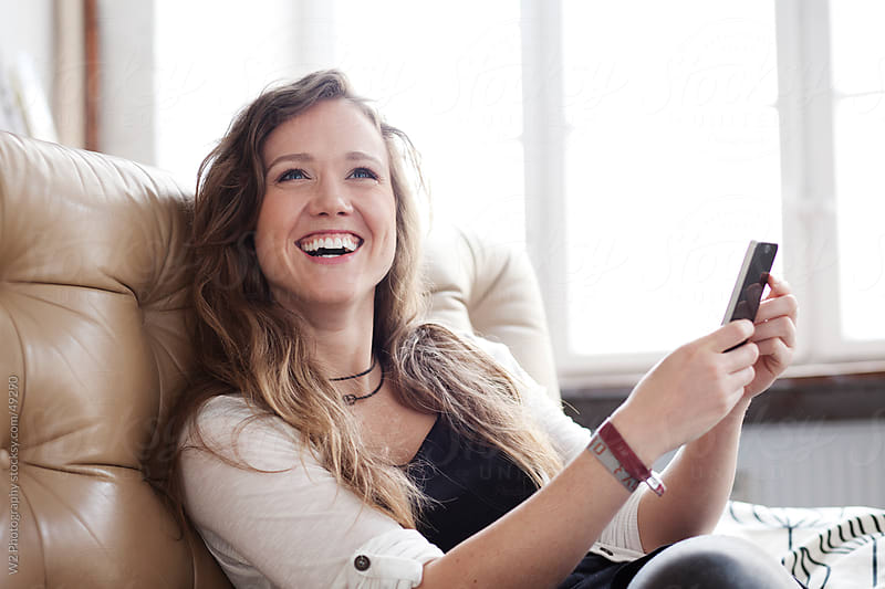 Beautiful smiling woman on a smartphone. by W2 Photography for Stocksy United