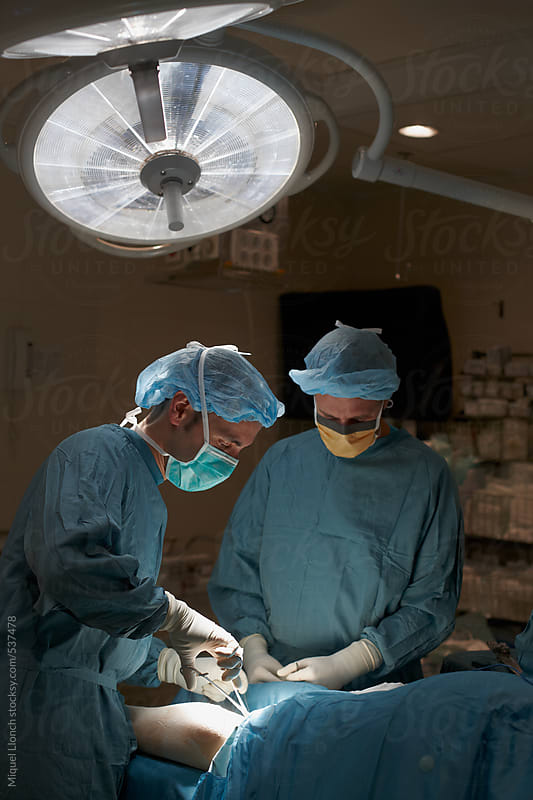 Two surgeons at work in the operating room by Miquel Llonch for Stocksy United