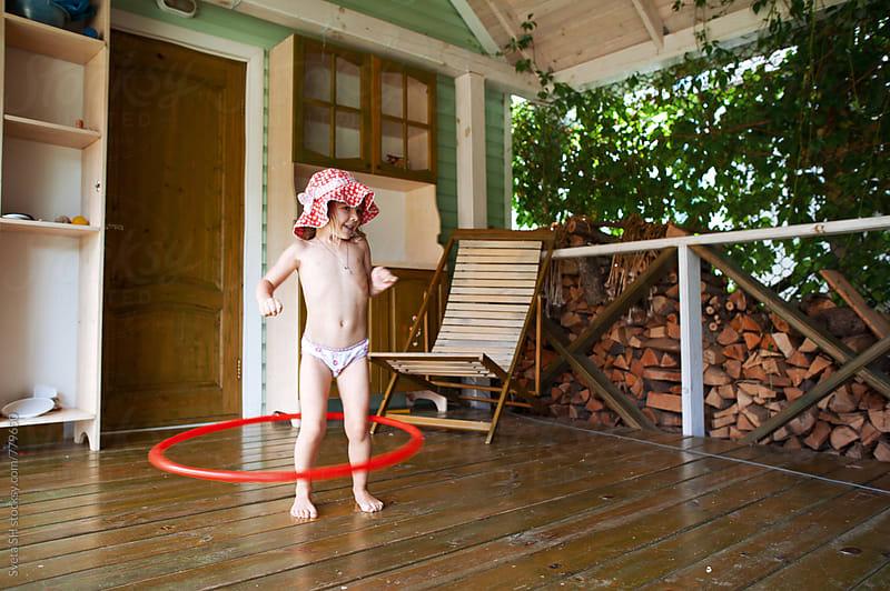 Little girl with a hula hoop. by Svetlana Shchemeleva for Stocksy United