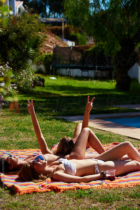 Three friends in bikini getting tanned on backyard by Guille Faingold for Stocksy United