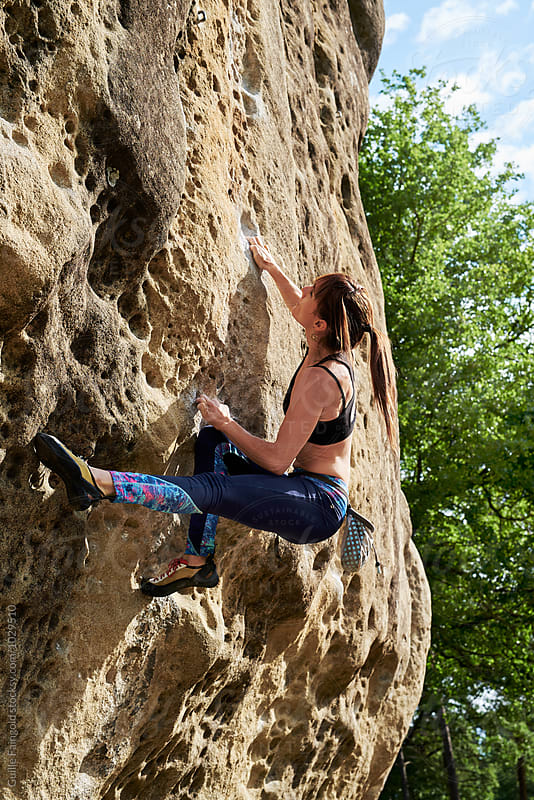Side view of strong brunette climbing the cliff with hands by Guille Faingold for Stocksy United