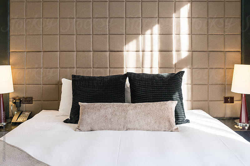 modern king size bed in an apartment by Gillian Vann for Stocksy United
