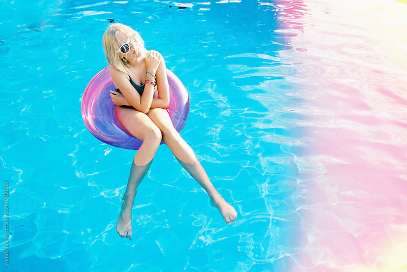 teen girl in pink floaty in swimming pool with blue water with light leaks by wendy laurel for Stocksy United