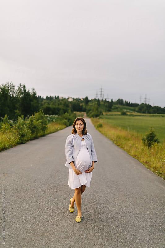 Pregnant female standing on the road by Evgenij Yulkin for Stocksy United