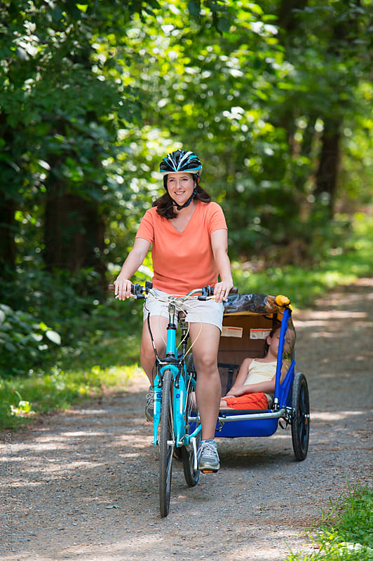 Family Bike Ride: Mother Tows Sleeping Daughter on Wooded Path by Brian McEntire for Stocksy United