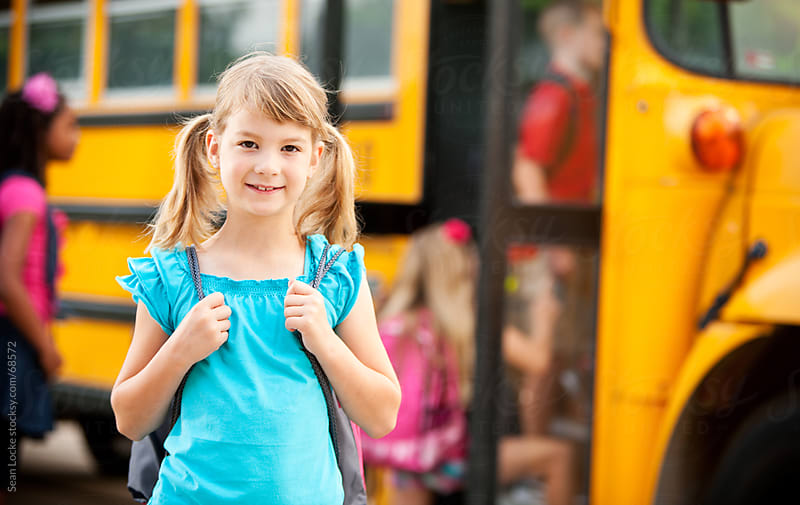 School Bus: Young Girl with Backpack by Sean Locke for Stocksy United