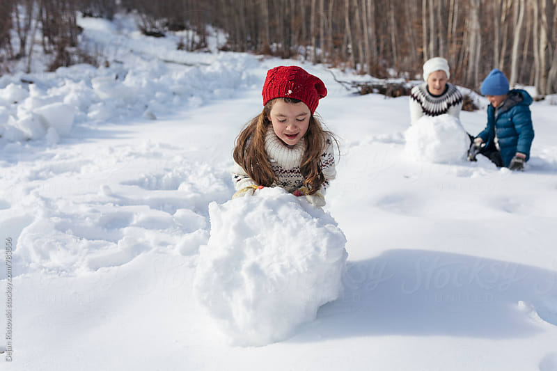 Family rolling a big snowballs. by Dejan Ristovski for Stocksy United