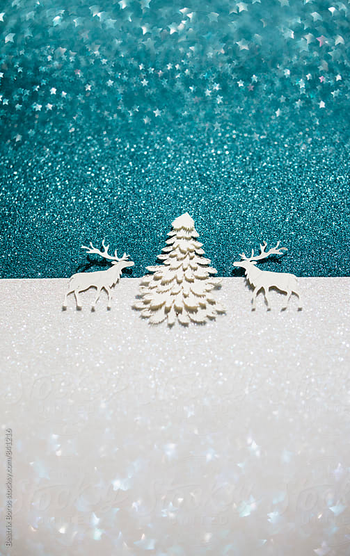 Festive scene with two deers and a pine tree on star shaped glitter blurry background by Beatrix Boros for Stocksy United