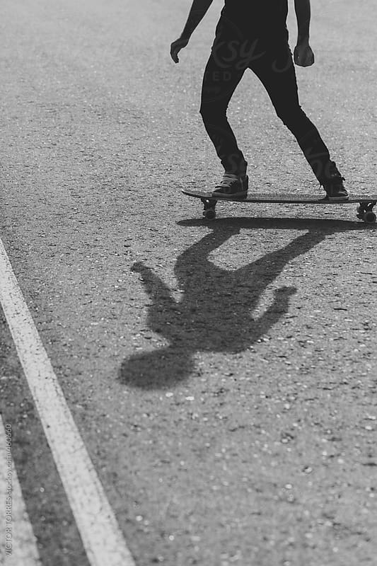 Shadow of a Young Man Longboarding in the Street by VICTOR TORRES for Stocksy United