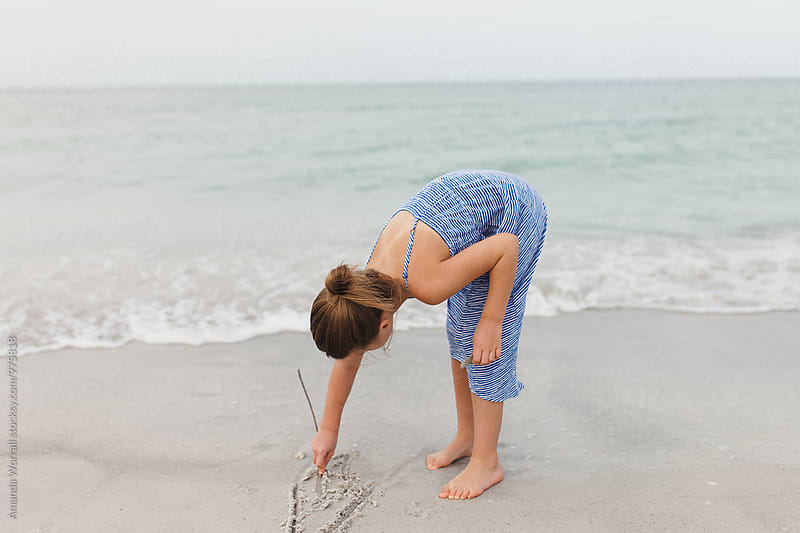 Girl using a stick to scratch in the sand by Amanda Worrall for Stocksy United