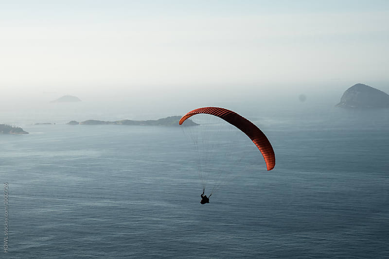 Brave parasail glides over the beaches of  rio de aneiro by HOWL for Stocksy United