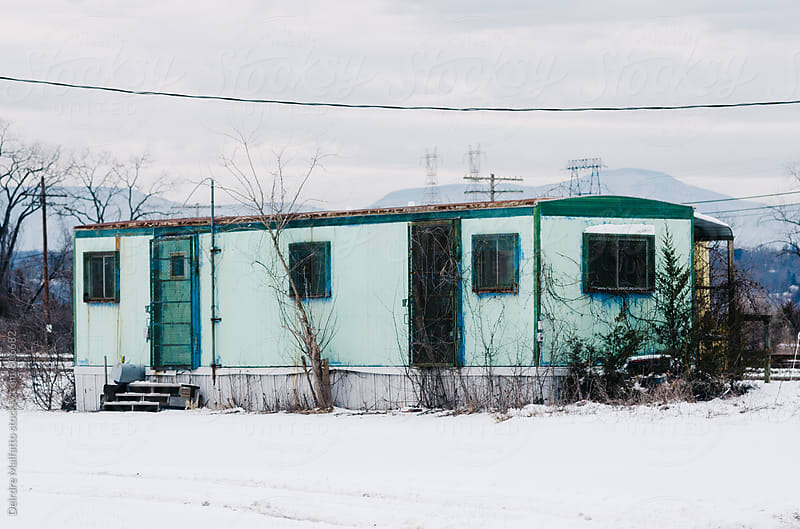 forlorn green trailer in the snow by Deirdre Malfatto for Stocksy United