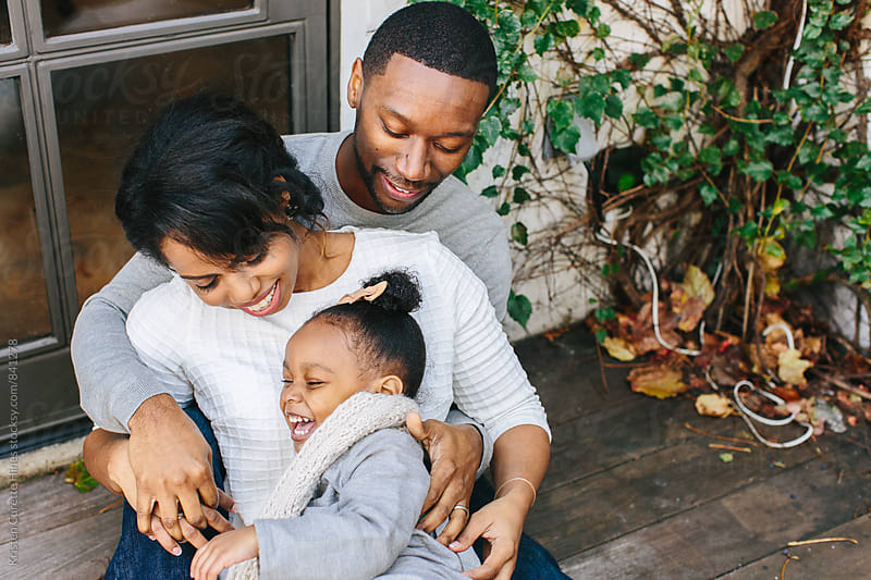 An adorable family of three embracing and smiling. Enjoying the little moments with family  by Kristen Curette Hines for Stocksy United