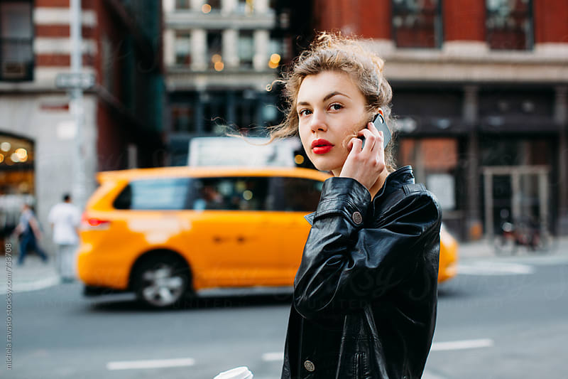 Attractive woman using mobile phone in the street by michela ravasio for Stocksy United