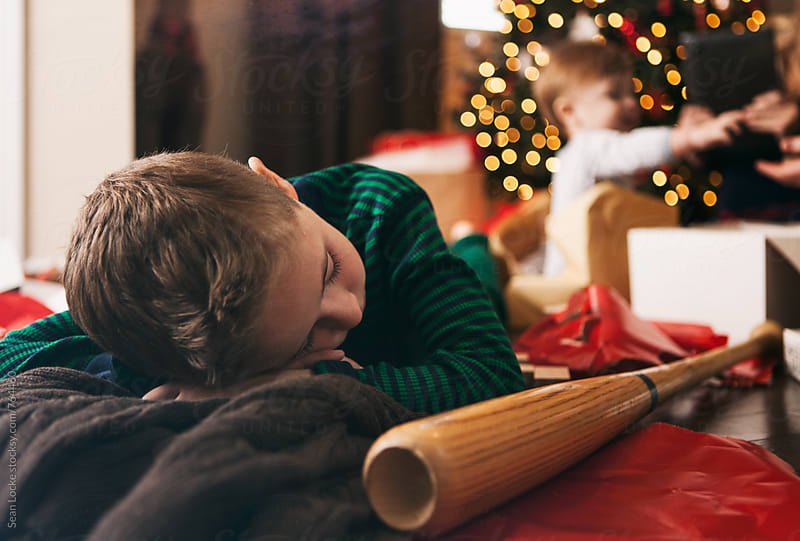 Christmas: Boy Asleep After Opening Christmas Gifts by Sean Locke for Stocksy United