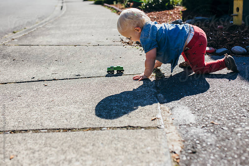 Toddler boy cralws after Wooden Train on the Sidewalk by Amanda Voelker for Stocksy United