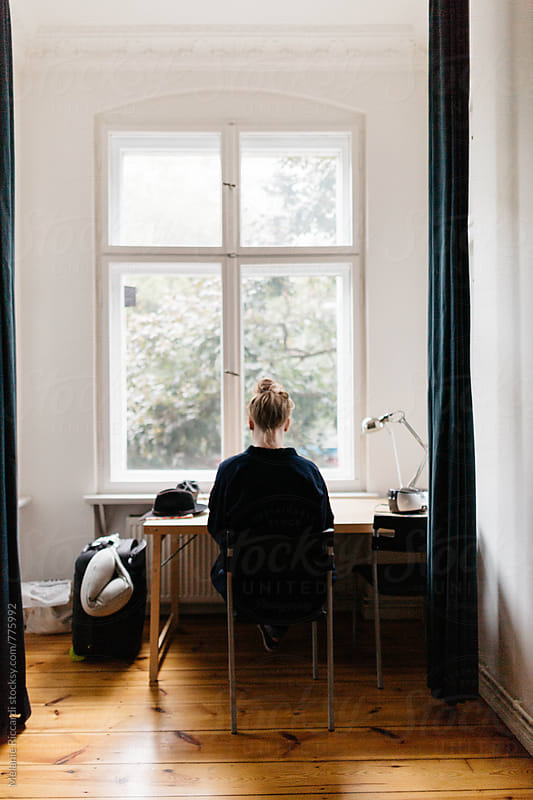 Woman sitting at Desk in front of window by Melanie Riccardi for Stocksy United
