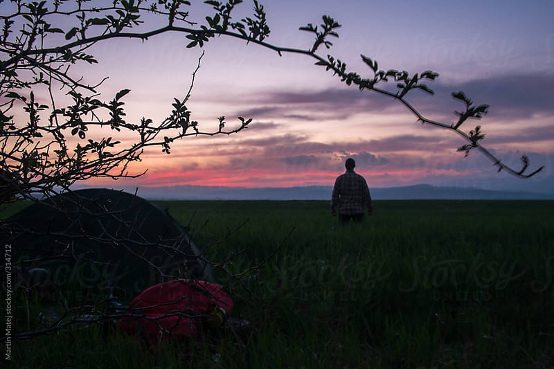 Young cyclist standing in the field by his tent and bicycle and watching sunset by Martin Matej for Stocksy United