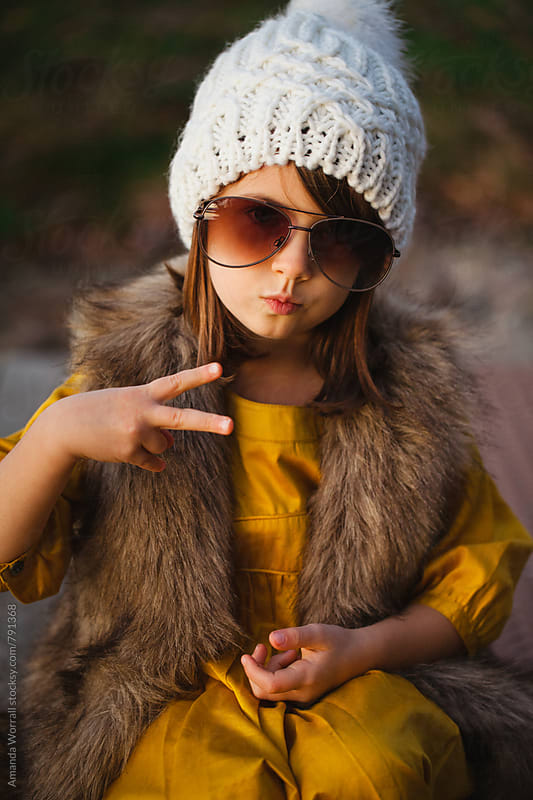 Hip and stylish little girl posing for the camera in autumn by Amanda Worrall for Stocksy United