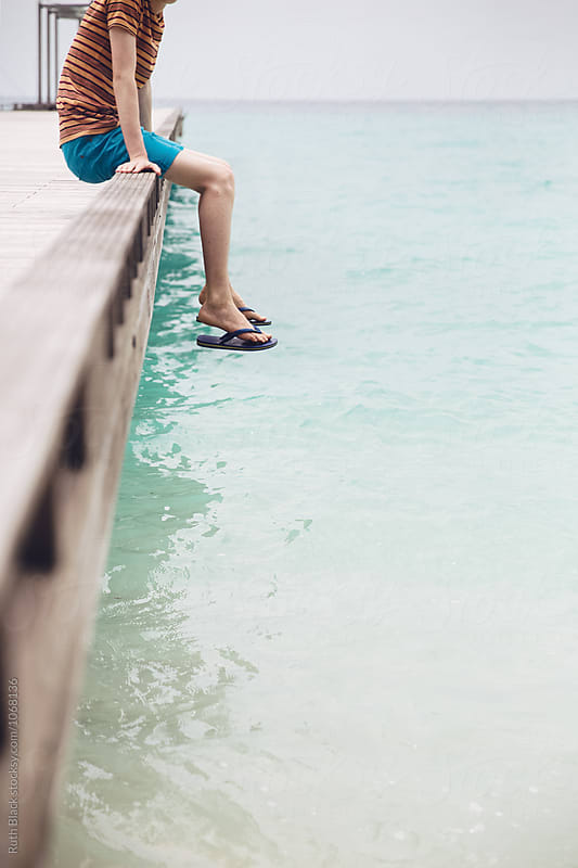 Boy sitting on the edge of the jetty by Ruth Black for Stocksy United