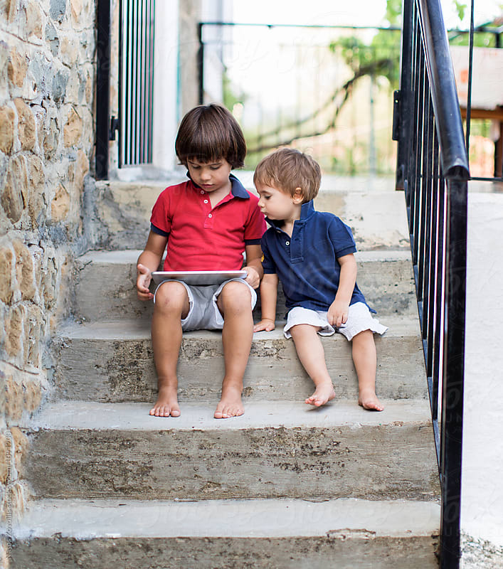 1 year old boy and his 5 year old brother using a digital tablet outdoor by Nasos Zovoilis for Stocksy United
