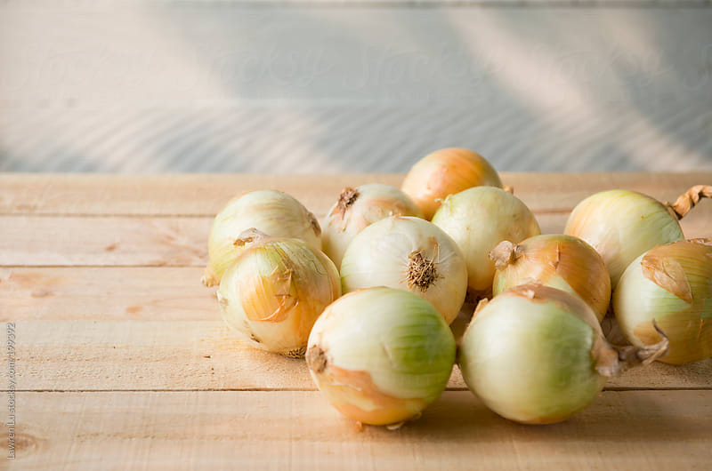 Onions on wooden board by Lawren Lu for Stocksy United