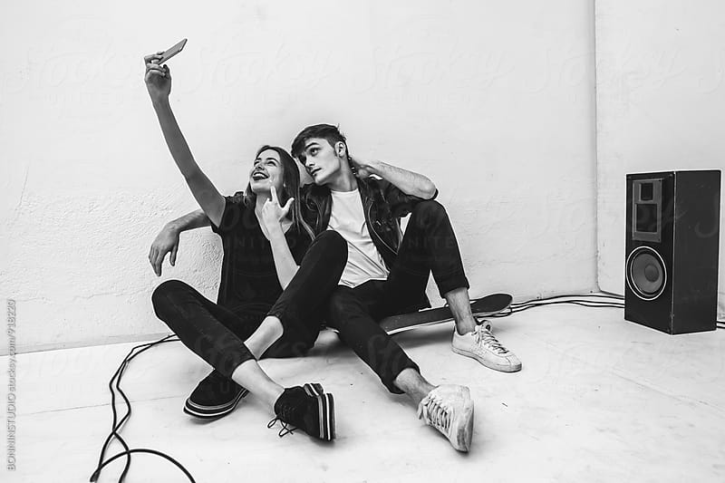 Rockers couple with their smartphone taking a selfie. by BONNINSTUDIO for Stocksy United