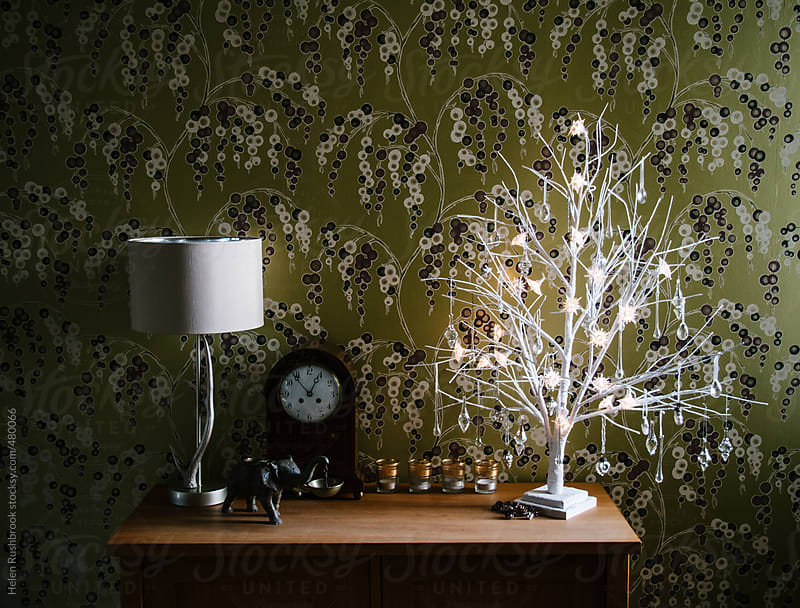 Home interior with white branches decorated with crystal, glass and silver Christmas decorations. by Helen Rushbrook for Stocksy United