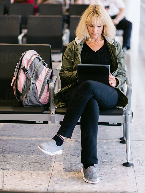 Woman Using TAblet Computer in Airport Lounge by Jeff Wasserman for Stocksy United