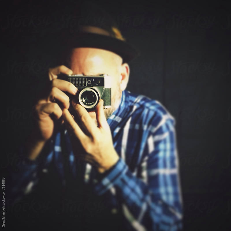 Portrait of a man with an old camera and hat by Greg Schmigel for Stocksy United